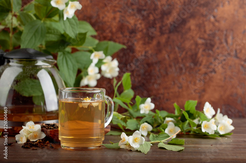 Leinwanddruck Bild Green tea with jasmine in cup and teapot on old wooden table.