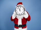 Santa Claus holding clock in front of his face - 226012852