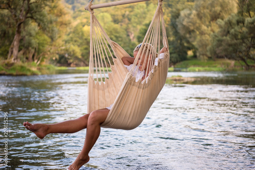 Leinwanddruck Bild blonde woman resting on hammock