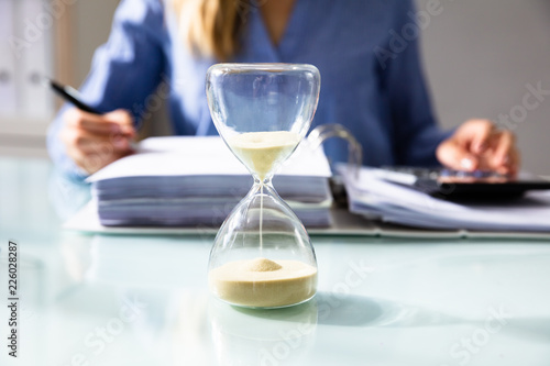 Close-up Of A Hourglass On Desk - 226028287
