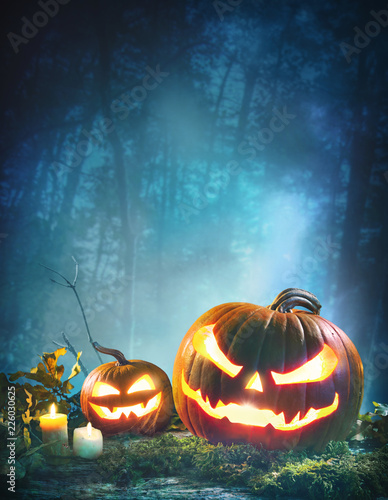 Leinwanddruck Bild Jack o' lanterns glowing at moonlight in front of spooky forest