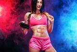 Muscular young fit sports woman athlete. Workout with bands or expander in gym on black background with colo smoke. Studio shot.