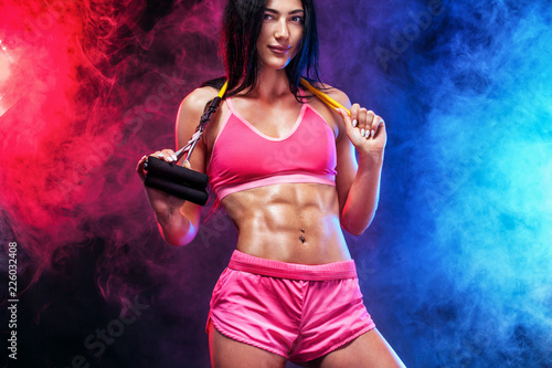 Muscular young fit sports woman athlete. Workout with bands or expander in gym on black background with colo smoke. Studio shot. - 226032408