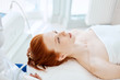 Attractive red haired woman lying on couch in medical centre, waiting for beauty massage. Facial treatment. Cosmetology, beauty and skin care and treatment concept .