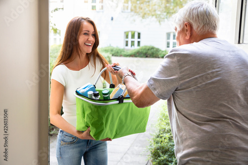 Leinwanddruck Bild Man Offering Help To His Daughter Carrying Groceries