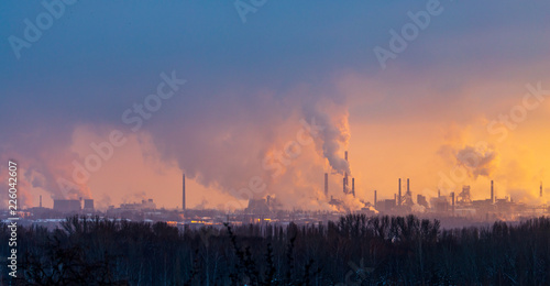 Smoke from the factory pipes against the dawn of the sun