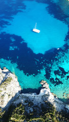 Aerial drone bird's eye view photo of tropical white rocky bay of Erimitis with turquoise clear waters and sail boats docked, island of Paxos, Ionian, Greece