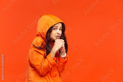 The young girl posing at studio in autumn jacket isolated on red. Human negative emotions. Concept of the cold weather. Female fashion concepts - 226058200