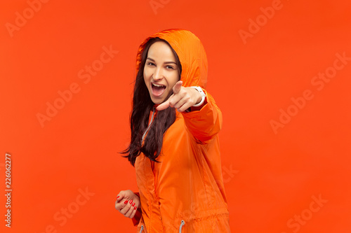 The happy smiling young girl posing at studio in autumn orange jacket pointing to camera isolated on red. Human positive emotions. Concept of the cold weather. Female fashion concepts - 226062277