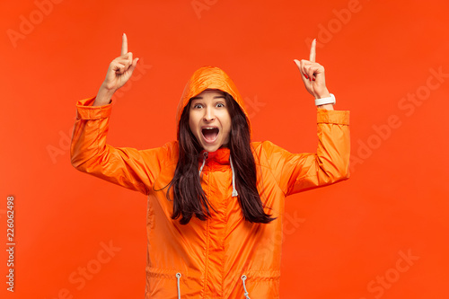 The happy smiling young girl posing at studio in autumn orange jacket pointing up isolated on red. Human positive emotions. Concept of the cold weather. Female fashion concepts - 226062498