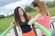 Women on outdoor exercise equipment