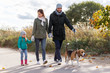 Leinwanddruck Bild - family, pets and people concept - happy mother, father and little daughter walking with beagle dog in autumn