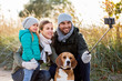 Leinwanddruck Bild - family, pets and people concept - happy mother, father and little daughter with beagle dog taking picture by smartphone on selfie  stick outdoors in autumn
