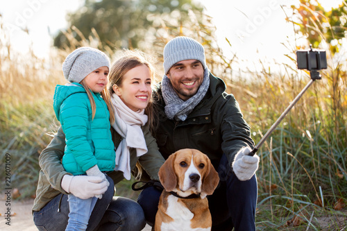Leinwanddruck Bild family, pets and people concept - happy mother, father and little daughter with beagle dog taking picture by smartphone on selfie  stick outdoors in autumn