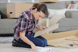 frustrated woman with self assembly furniture in kitchen - 226082419