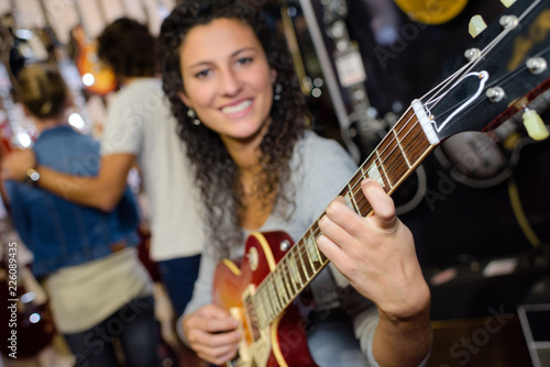 young woman playing a guitar - 226089435