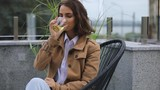 Young woman drinking hot green tea at the outdoor cafe, cold autumn day - 226093249