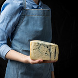 Woman in apron holding piece of blue cheese Gorgonzola on dark background