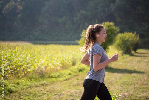 Foto Murales woman jogging along a country road
