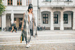 Leinwanddruck Bild - Woman in trend multilayered outfit walks in autumn city street. Fashion street trends