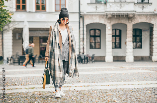 Leinwanddruck Bild Woman in trend multilayered outfit walks in autumn city street. Fashion street trends
