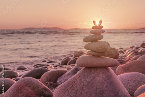 Pyramid of pebbles against the backdrop of the sea and sunset. The sun's rays shine through the cairn. - 226156062