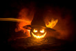 Quadro Halloween concept. Jack-o-lantern smile and scary eyes for party night. Close up view of scary pumpkin with witch hat on at dark foggy background. Selective focus.