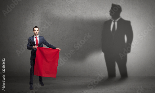 Leinwanddruck Bild Businessman standing with red cloth on his hand and his shadow on the background