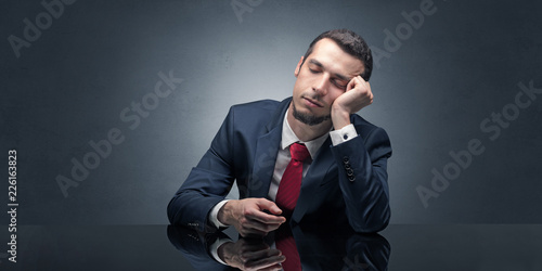 Leinwanddruck Bild Young businessman fell asleep at his workplace with copy space