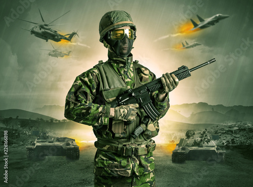 Fototapeta Armed soldier with sniper in the middle of a war