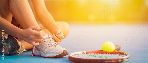 Fototapeta Tennis player tying shoelaces in court