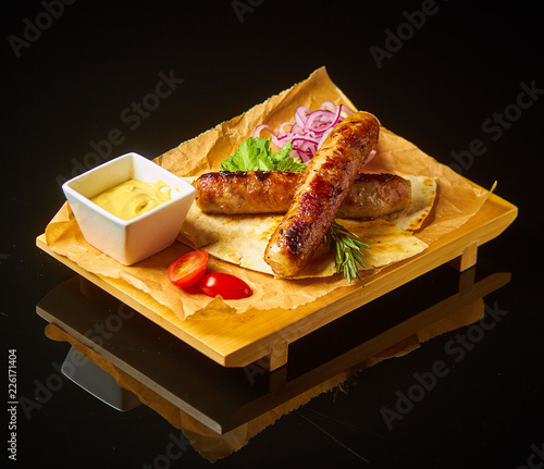German sausages with sauce on black mirror background - 226171404
