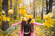 Autumn, joy and people concept - young woman having fun in autumn park. She is throwing yellow leaves in a sky