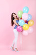 Young girl with colored balloons on pink background