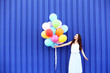 Cute girl with colored balloons on blue background