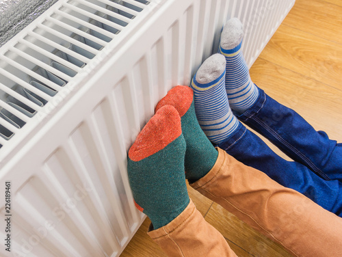 Leinwandbild Motiv Woman and child wearing colorful pair of woolly socks warming cold feet in front of heating radiator in winter time. Electric or gas heater at home.
