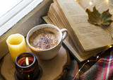 Cozy still life autumn coffee cup with scented candle and old book, fall cozy lifestyle
