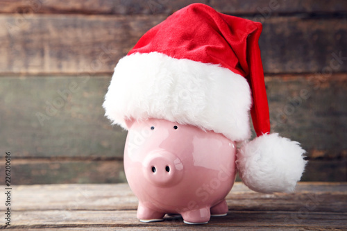 Leinwandbild Motiv Red santa hat with piggy bank on grey wooden table