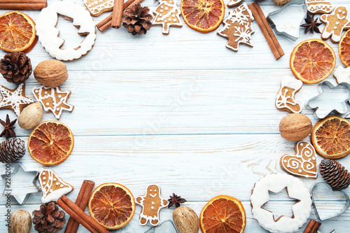 Leinwandbild Motiv Christmas gingerbread cookies with dry oranges and walnuts on white wooden table