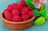 A dish of fresh ripe juicy raspberries, with mint and lime