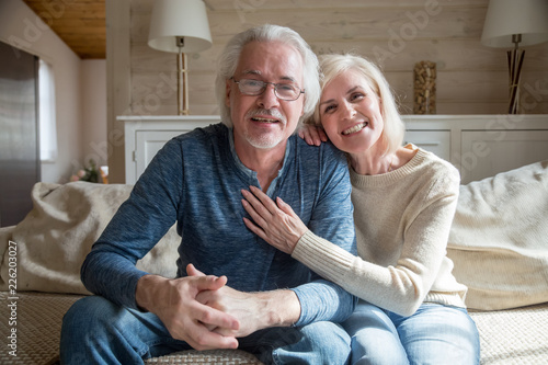 Leinwanddruck Bild Smiling senior middle aged vloggers couple looking talking at camera recording video blog at home, happy friendly mature old family making videocall sitting on sofa, elderly lifestyle vlog concept