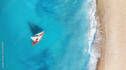 fototapeta na ścianę Yacht on the water surface from top view. Turquoise water background from top view. Summer seascape from air. Travel concept and idea