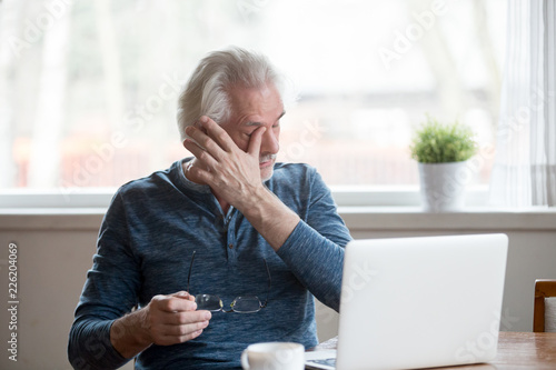 Leinwandbild Motiv Fatigued mature old man taking off glasses suffering from tired dry irritated eyes after long computer use, senior middle aged male feels eye strain problem or blurry vision working on laptop at home