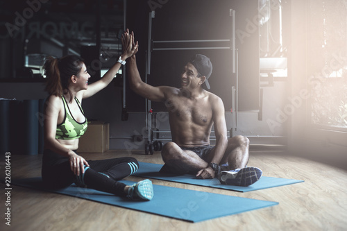 Sticker fit young man and woman sitting and giving each other high five at gym.