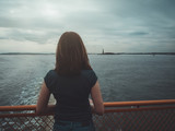 Woman on her back, observing in the distance, the statue of liberty, clinging to the railing of a ship, in New York, USA