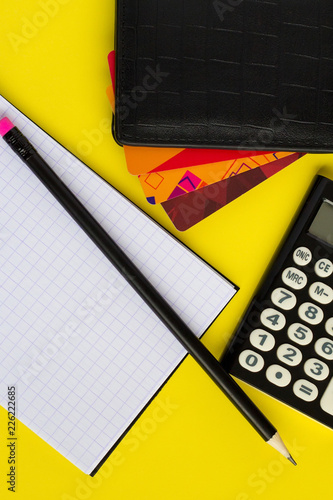 Flat lay composition with notepad, pencil, wallet with different credit cards and calculator on yellow bright background - 226222685
