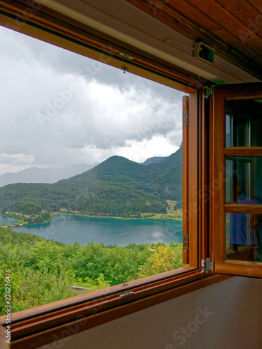 Foto Murales wooden window frame with view to a mountain lake, fall weather