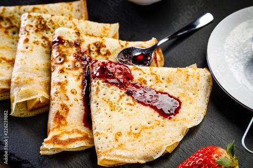 Leinwandbild Motiv Crepes with strawberries and jam