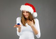 Leinwandbild Motiv Beautiful woman in Santa Claus clothes holding gift boxes on gray background