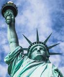 Estatua de la libertad, vista desde un ángulo bajo, con fondo nublado y cielo azul, en la Isla de la Libertad de Nueva York, EE. UU.,